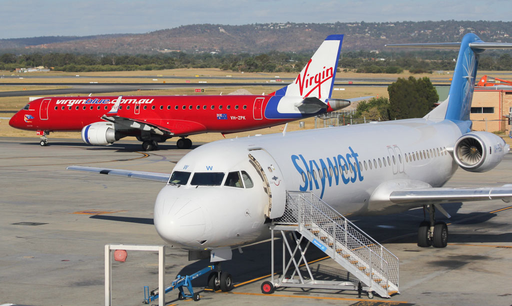 ABOVE: A Virgin Embraer E190 taxying out behind a Skywest Fokker 100. The Shywest brand will soon disappear from West Australian skies.  Photo © David Eyre