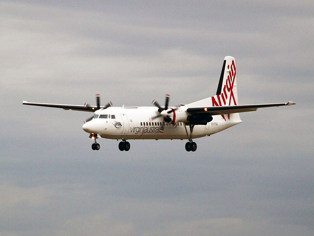 "VH-FNA Fokker 50 (cn 20106) of Skywest / Virgin Australia Regional Airlines, named ""Rockingham Beach"", at Perth Airport - Wed 1 May 2013. Landing on runway 03 at 17:12 on a flight from Onslow.  This aircraft was flown from Perth via Alice Springs to Townsville on 25 February 2013 and was repainted all-white with no titles, but still had the rudder painted in Skywest colours. The takeover of Skywest by Virgin Australia was still awaiting some regulatory approvals, so it could not be painted in Virgin Australia colours at that time. VH-FNA returned to Perth on 11 March 2013, and re-entered service. On 20 April 2013, it was again flown Perth-Alice Springs-Townsville and became the first Skywest Fokker 50 to be painted in Virgin Australia colours. It returned to Perth via Alice Springs on 26 April 2013, and now wears the name ""Rockingham Beach"" (it previously wore the name ""City of Albany"" when in Skywest colours).  Photo © Keith Anderson"