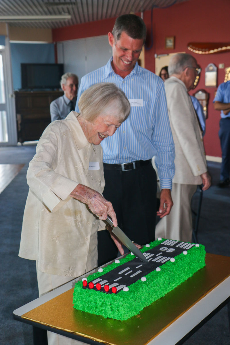 Shirley Adkins, OAM, cutting the cake with John Fraser, Managing Director of Jandakot Airport Holdings, at a celebration held in the Royal Aero Club of Western Australia, to mark the 50th Anniversary of Jandakot Airport - Thu 21 November 2013.