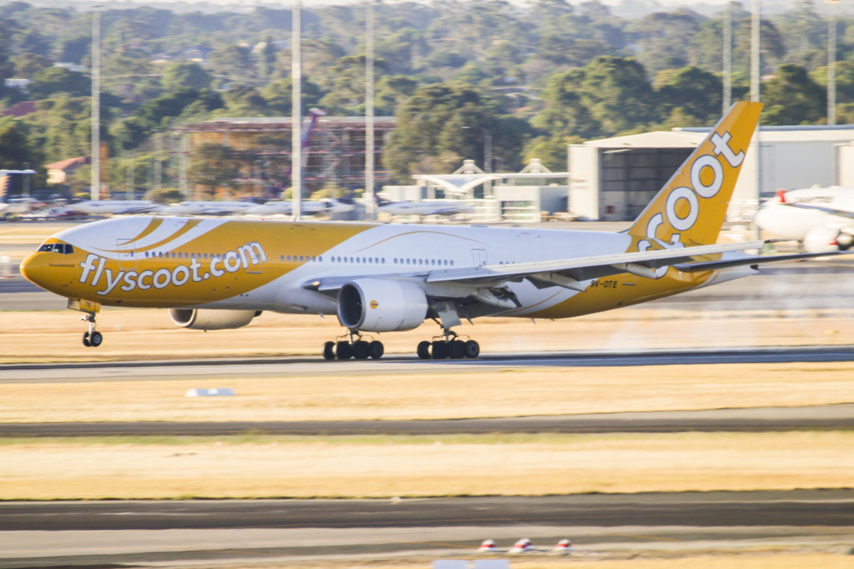 """9V-OTE Boeing 777-212ER (MSN 28519/237) of Scoot, named """"Scootalicious"""", at Perth Airport - Thursday 12 December 2013. **FIRST SERVICE TO PERTH, FIRST VISIT BY THIS AIRCRAFT SINCE WITH SCOOT** Inaugural service TZ8 / TZ7 between Singapore and Perth. Flight TZ8 is seen here landing on runway 21 at 18:10. It arrived at Bay 55 five minutes early, at 18:15, with Scoot CEO Campbell Wilson leaning out of the First Officer's cockpit window to wave to the assembled media representatives as it taxied in to the bay. A pair of traditional Chinese dragons danced amongst the crowds assembled near the Arrivals area inside the International Terminal (Terminal 1). The aircraft departed back to Singapore on time, with flight TZ7 taking off at 19:46 from runway 21. The five times per week service was originally to commence on 19 December 2013, but was brought forward by one week. This aircraft formerly visited Perth when with Singapore Airlines as 9V-SQH. Photo © David Eyre"""