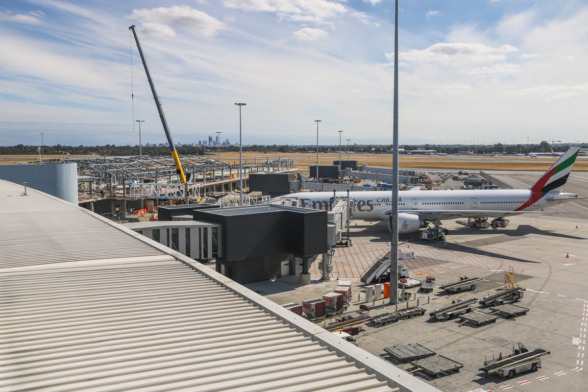Virgin Australia Pier under construction at Terminal 1 and A6-EGL Boeing 777-31H ER (MSN 41072/985) of Emirates at Perth Airport - Thu 17 April 2014. Photo © David Eyre