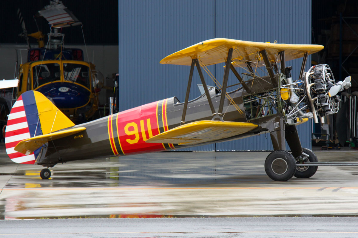 VH-PJS / (41-)911 Boeing Stearman PT-17 (A75L300) (MSN 75-671) owned by Robert Poynton, at Jandakot Airport - Sat 30 August 2014. Engine covers removed for maintenance. Built in 1943, ex 41-911 (USAAF), N52042, N59GA, VH-JBC. One of the McDermott Aviation Bell 214B-1 BigLifter firefighting helicopters is in the hangar behind. Photo © Steve Jaksic