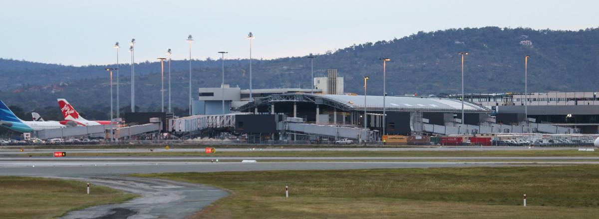 Terminal 1 and the new Virgin Australia Pier under construction, at Perth Airport - Tue 2 September 2014. The Virgin Pier is delayed to June 2015. At the extreme left is PK-GPE Airbus A330-341 (MSN 148) of Garuda Indonesia. Garuda has returned to using A330s on the Perth-Bali services, instead of 737-800s. PK-GPE was operating the first departure of the A330 since this type resumed service. Photo © David Eyre