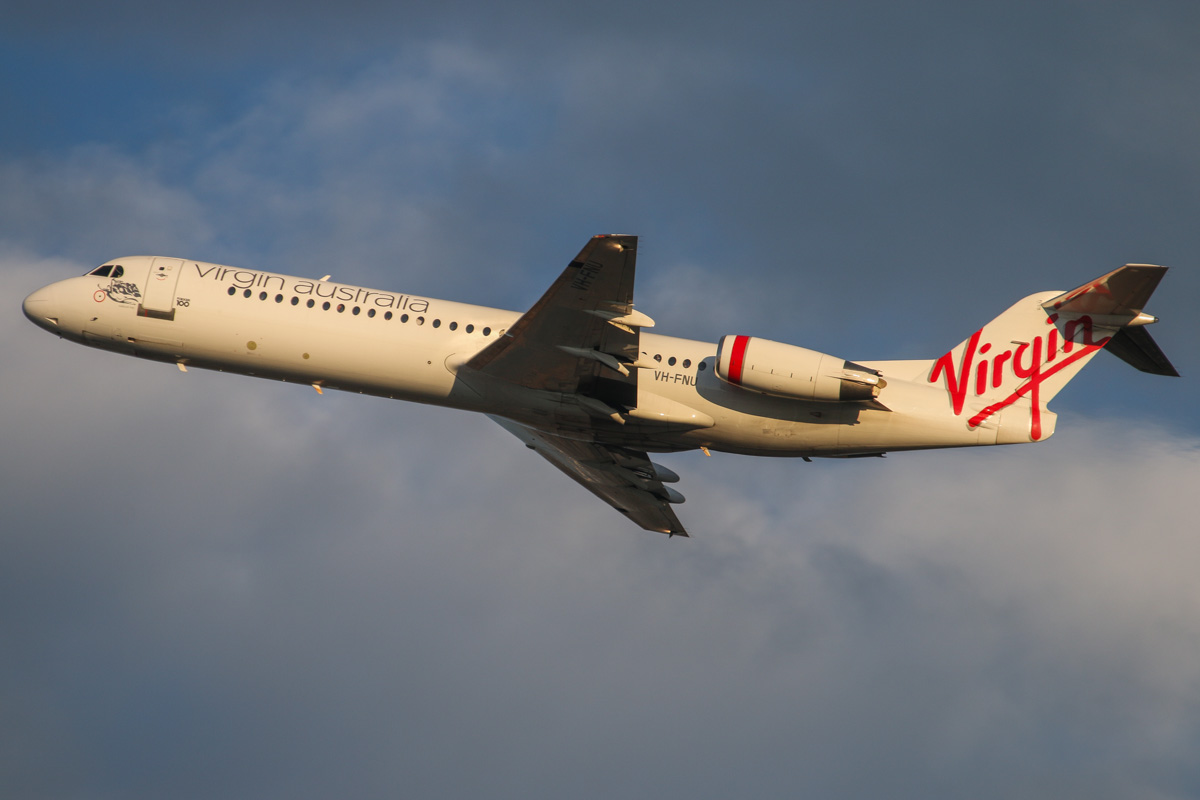 "VH-FNU Fokker 100 (MSN 11373) of Virgin Australia Regional Airlines, named ""Roebuck Bay"", at Perth Airport – Wed 3 September 2014. Flight VA9281 to Barimunya, seen after takeoff from runway 21 at 7:07am. Photo © David Eyre"