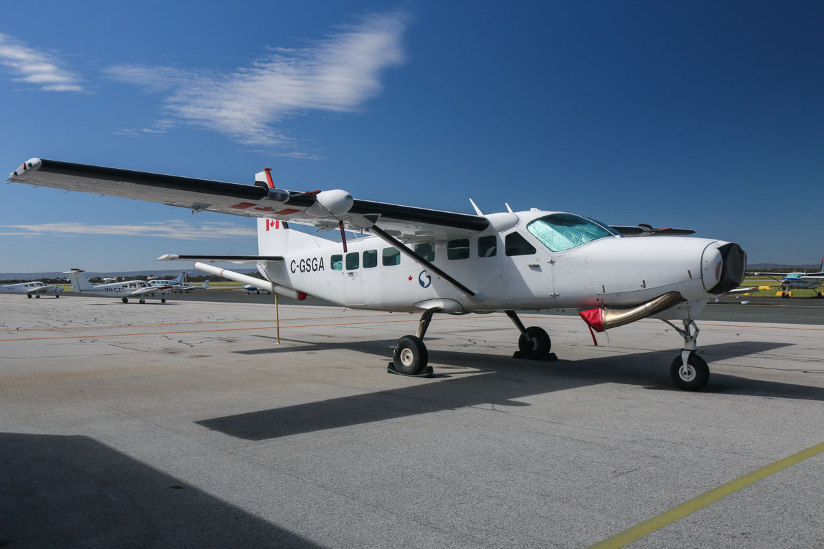 "C-GSGA Cessna 208B Grand Caravan (MSN 208B1228, ex N1084N), owned by Sander Geophysics Limited (Canada), at Jandakot Airport - Fri 5 September 2014. This flew Port Moresby (Papua New Guinea) to Cairns and Cloncurry in June 2014, before later arriving at Jandakot. It has been to Jandakot in the past, and has had its prop removed. the aircraft is used for geophysical surveys, detecting variations in the Earth's magnetic field caused by mineral bodies, using a magnetometer tail ""stinger"" boom. Photo © David Eyre"