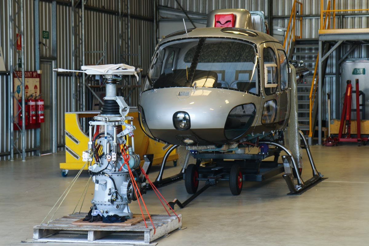 VH-... Eurocopter AS350 Squirrel at Jandakot Airport - Fri 5 September 2014. The main rotor transmission is sitting on a pallet in front, with the engine connection visible near the base, on the right side. Photo © David Eyre