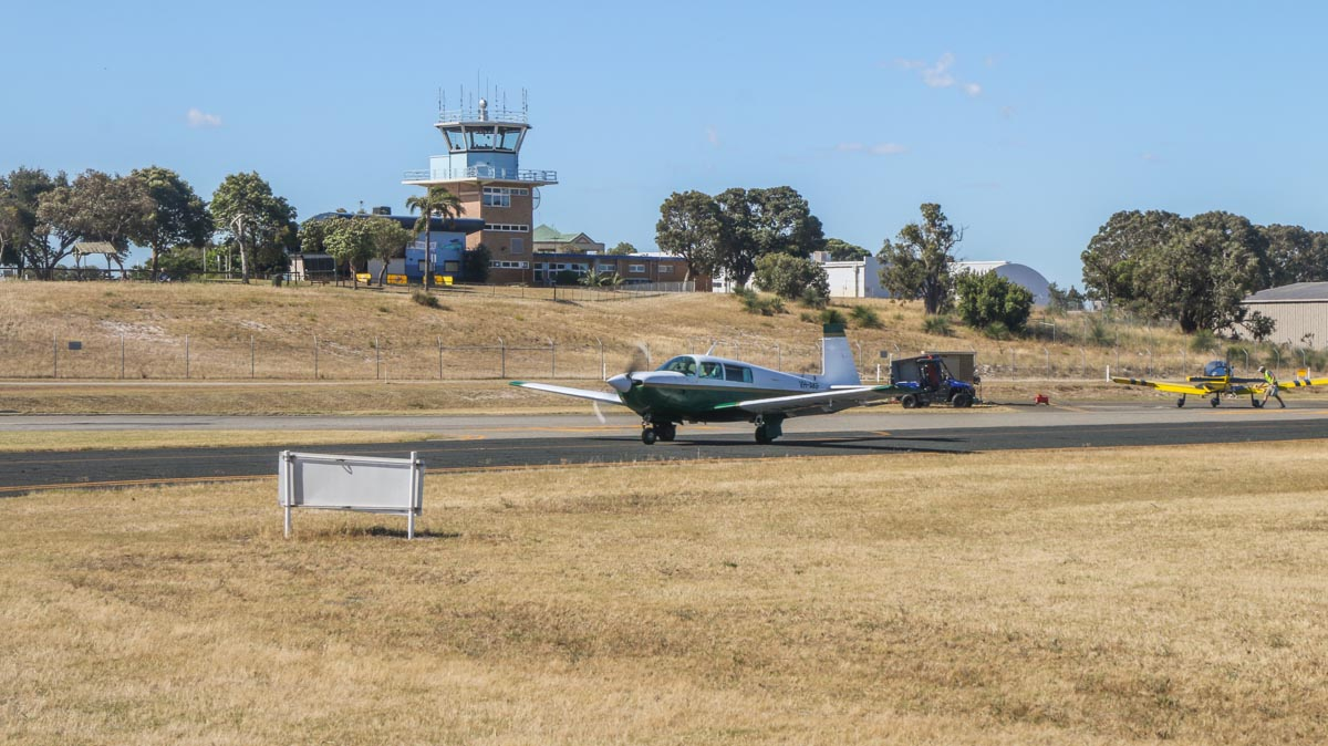 VH-AKF Mooney M20J 201 of Royal Aero Club of WA, taxying in front of the control tower at Jandakot Airport, seen from VH-LZJ SOCATA TBM 900 (MSN 1016) owned and flown by Jean-Jacques Bely, – Fri 14 November 2014. The Viewing Area is visible at upper left of photo. Photo © David Eyre