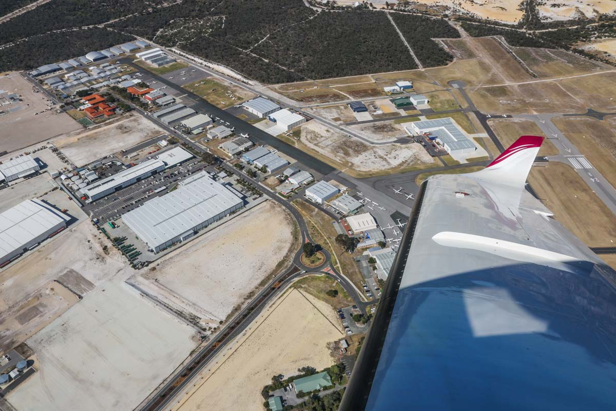 Jandakot Airport, seen from VH-LZJ SOCATA TBM 900 (MSN 1016) owned and flown by Jean-Jacques Bely, – Fri 14 November 2014. View facing east across the Northern Apron, as we join the downwind leg for runway 24R. At upper left are the red-roofed buildings of Singapore Flying College, which trains pilots for Singapore Airlines. The large hangar above the wingtip is the WA Police Air Wing. Photo © David Eyre