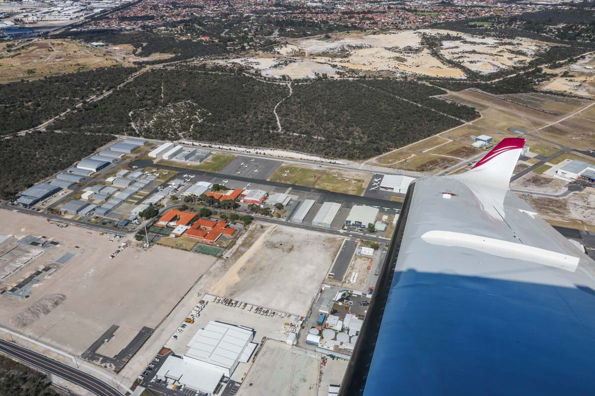 Jandakot Airport, seen from VH-LZJ SOCATA TBM 900 (MSN 1016) owned and flown by Jean-Jacques Bely, – Fri 14 November 2014. View facing ESE across the Northern Apron, as we join the downwind leg for runway 24R. At left are the red-roofed buildings of Singapore Flying College, which trains pilots for Singapore Airlines. At right edge is the WA Police Air Wing hangar. At left edge is Heliwest. Photo © David Eyre