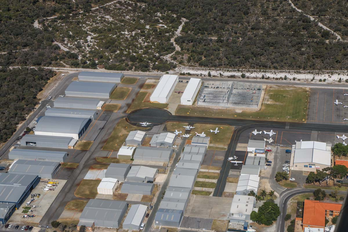 Jandakot Airport, seen from VH-LZJ SOCATA TBM 900 (MSN 1016) owned and flown by Jean-Jacques Bely, – Fri 14 November 2014. View facing ESE across the Northern Apron, as we flew the downwind leg for runway 24R. At bottom left is Heliwest and centre right edge is Premiair's hangar, next to the red-roofed buildings of Singapore Flying College, which trains pilots for Singapore Airlines. Photo © David Eyre