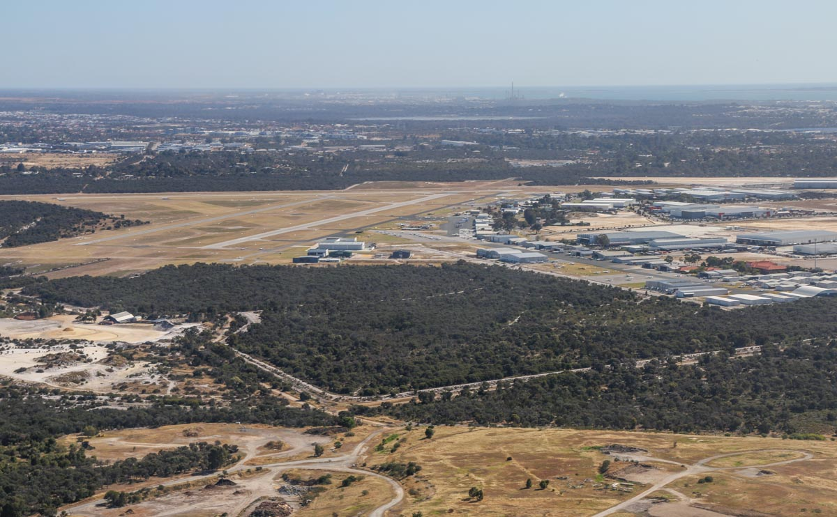 Jandakot Airport, seen from VH-LZJ SOCATA TBM 900 (MSN 1016) owned and flown by Jean-Jacques Bely, – Fri 14 November 2014. View facing west across the airport, as we join the base leg for runway 24R. Photo © David Eyre