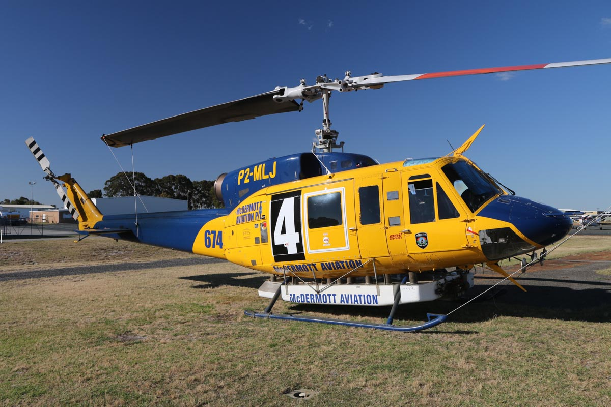 "P2-MLJ / HELITAK674 / 4 Bell 214B1 BigLifter (MSN 28066) owned by McDermott Aviation, operated for the Department of Fire and Emergency Services, at Jandakot Airport – Fri 14 November 2014. One of six Bell 214B1s of McDermott Aviation based in WA for the 2014/15 bush fire season (October – April). Fitted with the Isolair 'Tsunami"" Belly Tank, with 2,700 Litres capacity. Built in 1981, ex N2179R, JA9304, N4410N, C-GTWG, F-GJKZ, N214JL. Photo © David Eyre"