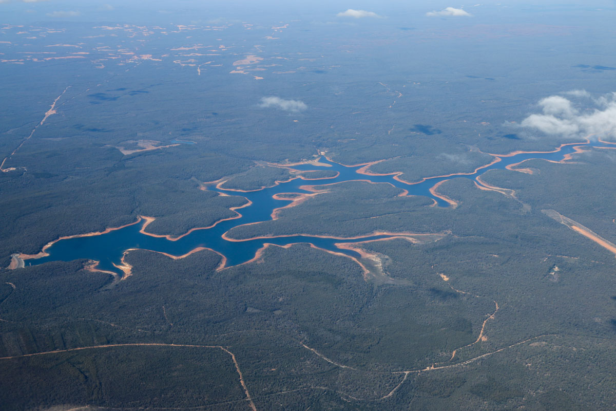 South Dandalup Dam and Lake Banksiadale, seen from VH-LZJ SOCATA TBM 900 (MSN 1016) owned and flown by Jean-Jacques Bely, – Fri 14 November 2014. Taken from an altitude of 16,500 feet, en route from Manjimup, heading north to Jandakot. View northeast. The dam was built in 1971 and is the largest dam supplying Perth with water. Dwellingup Airstrip is visible at the right edge of photo - this is used by the Department of Parks and Wildlife for its fire spotter aircraft. Photo © David Eyre