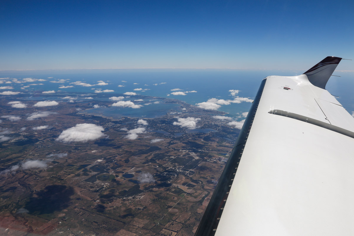 Aboard VH-LZJ SOCATA TBM 900 (MSN 1016) owned and flown by Jean-Jacques Bely, over the town of Keysbrook, near Mandurah – Fri 14 November 2014. Taken at just over 21,000 feet, heading south to Manjimup. View southwest to the city of Mandurah and Peel Inlet (visible centre left), with Murrayfield Airfield just ahead of the leading edge. Photo © David Eyre