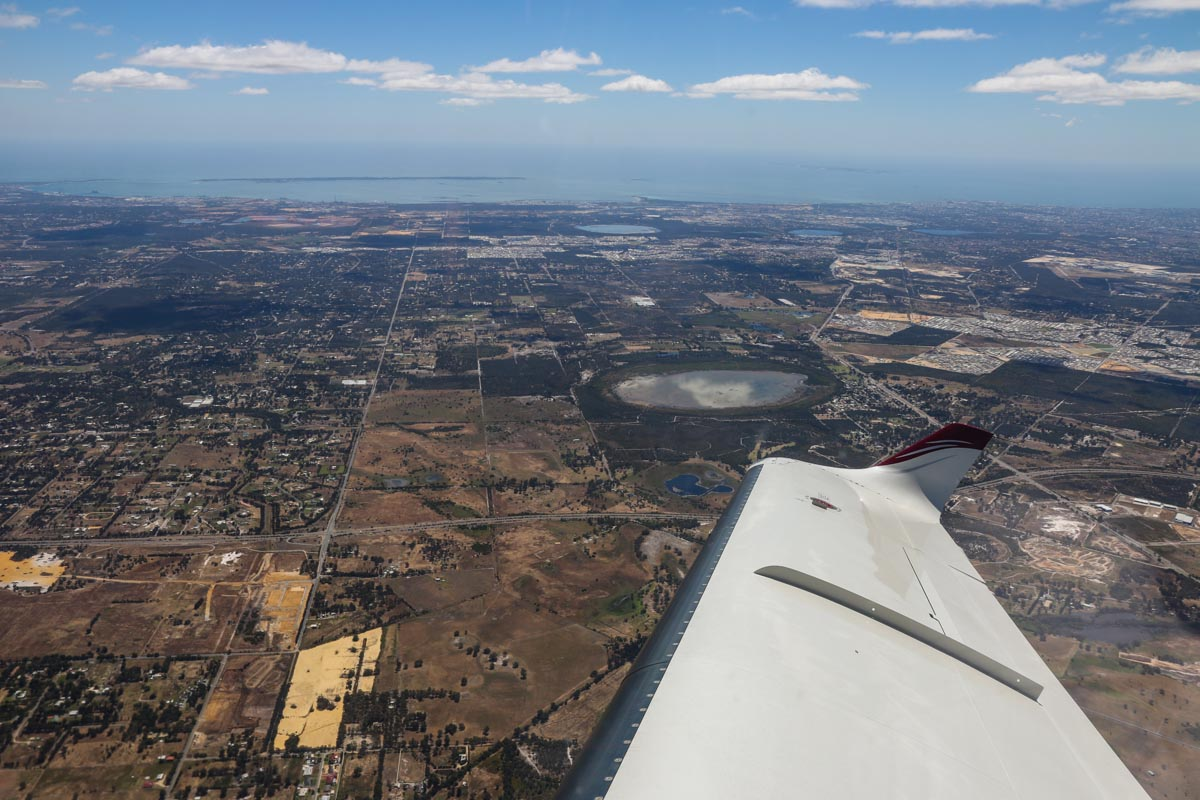 Aboard VH-LZJ SOCATA TBM 900 (MSN 1016) owned and flown by Jean-Jacques Bely, over the southern Perth suburb of Brookdale – Fri 14 November 2014. Taken at around 4,000 feet, shortly after take-off from Jandakot's runway 06L. This view facing west shows Forrestdale Lake is nearest to the wingtip, with Jandakot Airport and Fremantle are visible at upper right, Rockingham at upper left and Garden Island next to it. Photo © David Eyre