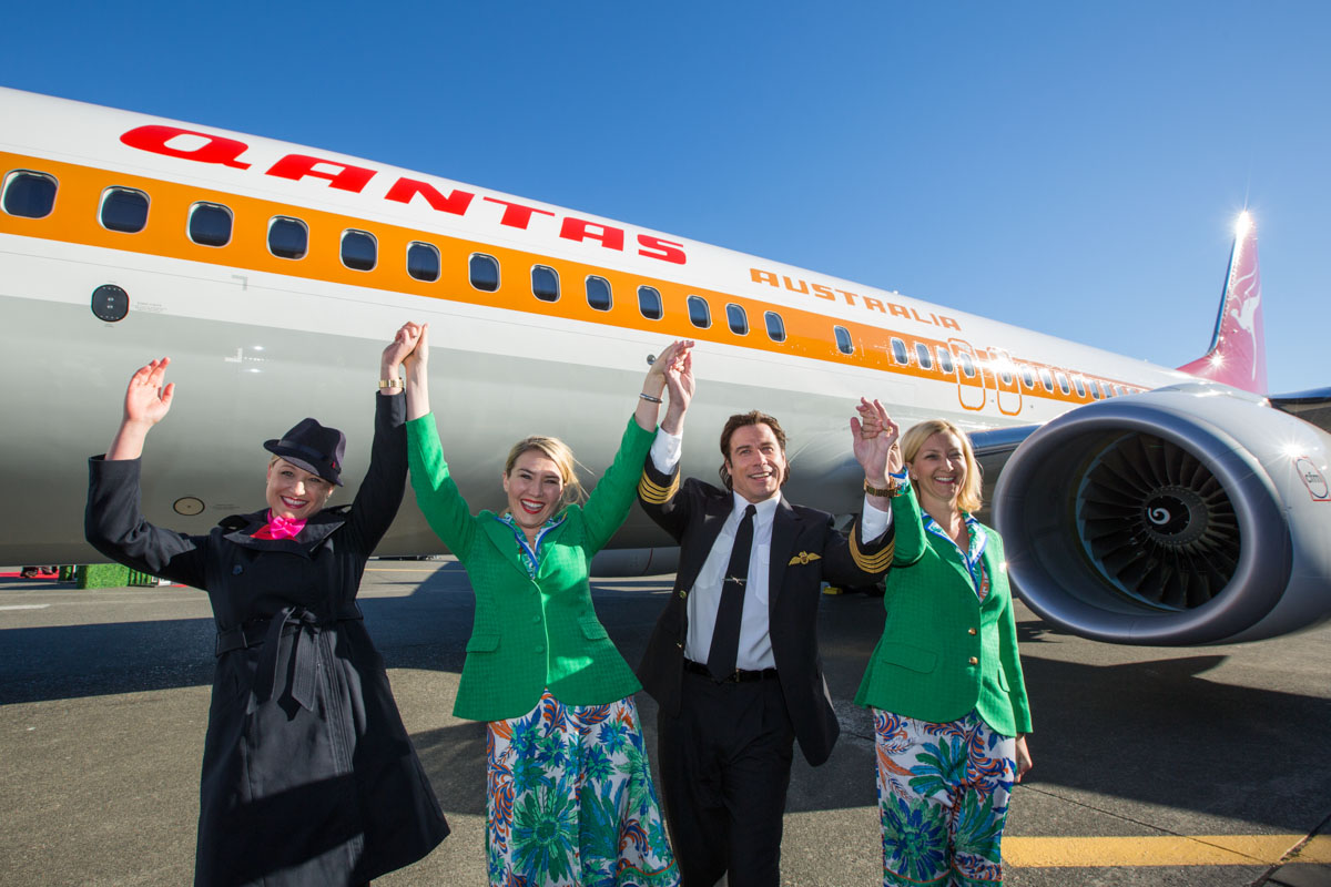 Actor and Qantas Ambassador John Travolta with Qantas flight attendants in 1970s uniforms, in front of VH-XZP Boeing_737-838 (MSN 44577/5164) of Qantas, named 'James Strong' in a retro livery worn by the airline in the 1970s, at the unveiling and handover ceremony at Boeing Field, Washington, USA - 16 November 2014.  Photo © Qantas