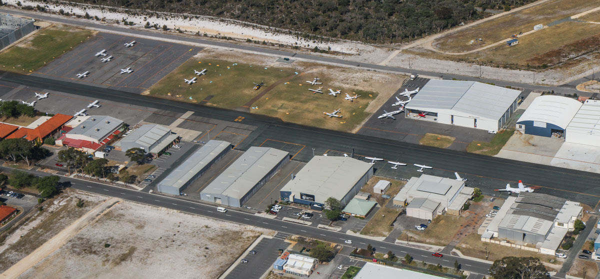 Jandakot Airport, seen from VH-LZJ SOCATA TBM 900 (MSN 1016) owned and flown by Jean-Jacques Bely, – Fri 14 November 2014. View facing east across the Northern Apron, as we fly the downwind leg for runway 24R. A number of geophysical survey aircraft are visible, distinctive with the magnetometer tail 'stingers' - this includes the CASA 212 used by CGG Airborne at the right of photo. In centre of photo is Polytechnic West with the Boeing 737-229 tail poking out the hangar. Upper right is Casair's maintenance facility with one of their Metro aircraft parked outside. At far left are the red-roofed buildings of Singapore Flying College, which trains pilots for Singapore Airlines, with some of their Cessna 172R and Beech Baron G58 aircraft visible opposite. Photo © David Eyre