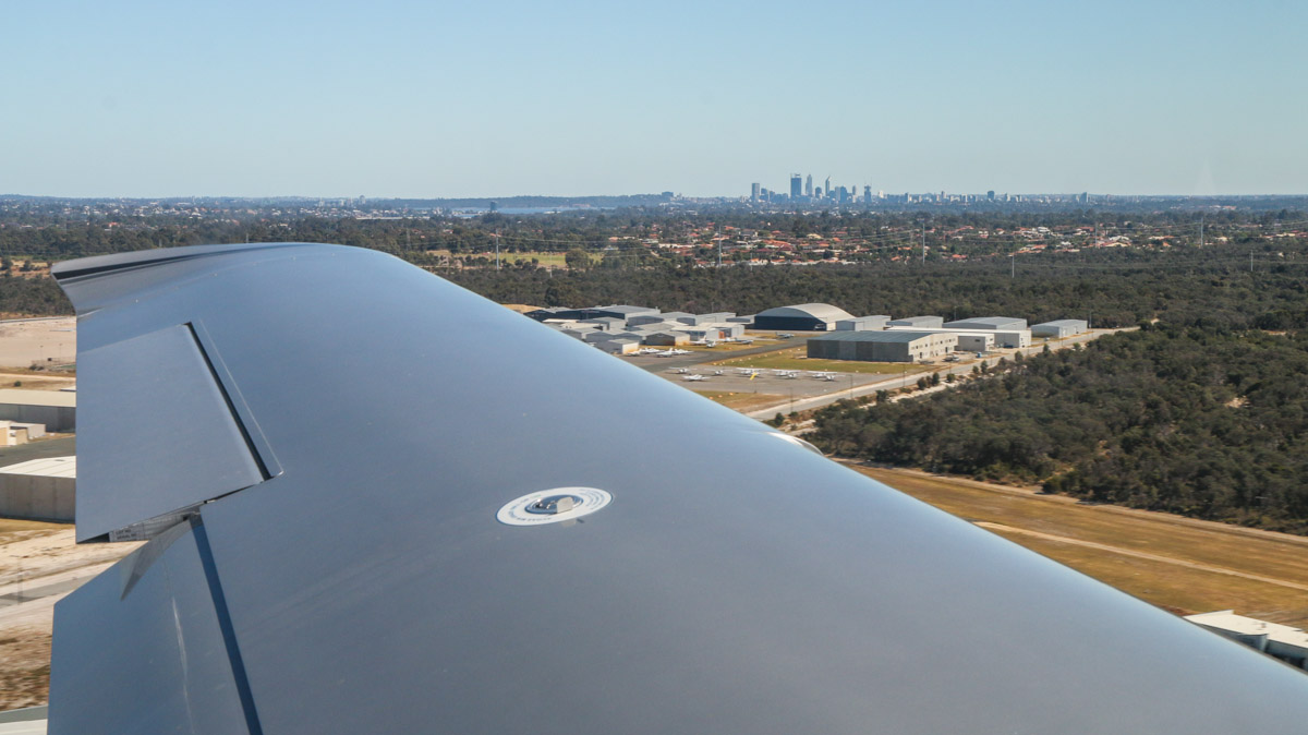 Jandakot Airport with Perth city in the distance, seen from VH-ICE Cirrus SR22 GTS G5 (MSN 4063) owned by Andrew Dean, at Jandakot Airport - Sat 15 November 2014. Take-off from runway 06L at 9:02am for a flight to Geraldton, Dongara and return, with some sightseeing along the way. Photo © David Eyre