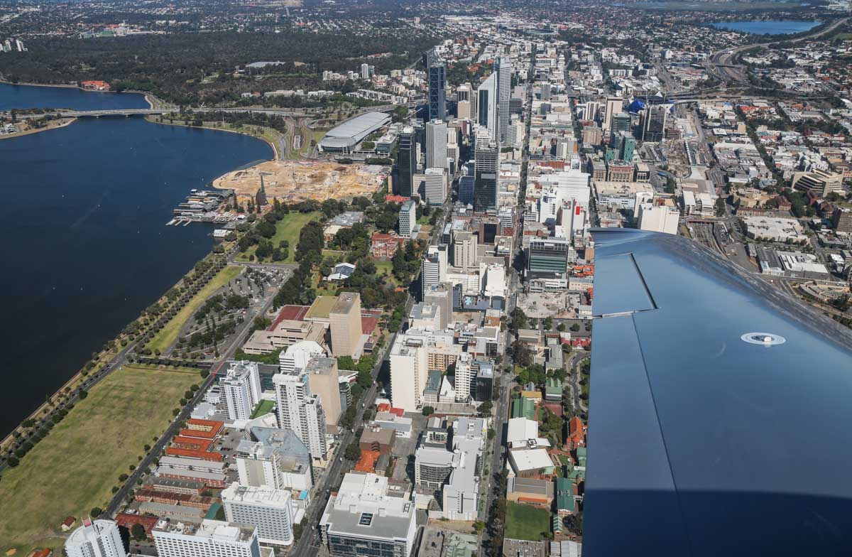 Perth city, Langley Park, Kings Park, Barrack Street Jetty, and Elizabeth Quay under construction, seen from VH-ICE Cirrus SR22 GTS G5 (MSN 4063) owned by Andrew Dean - Sat 15 November 2014. View facing WNW. The grass area at lower left is the part of Langley Park which was used as Perth's first airport, from late 1919 to January 1924. Photo © David Eyre