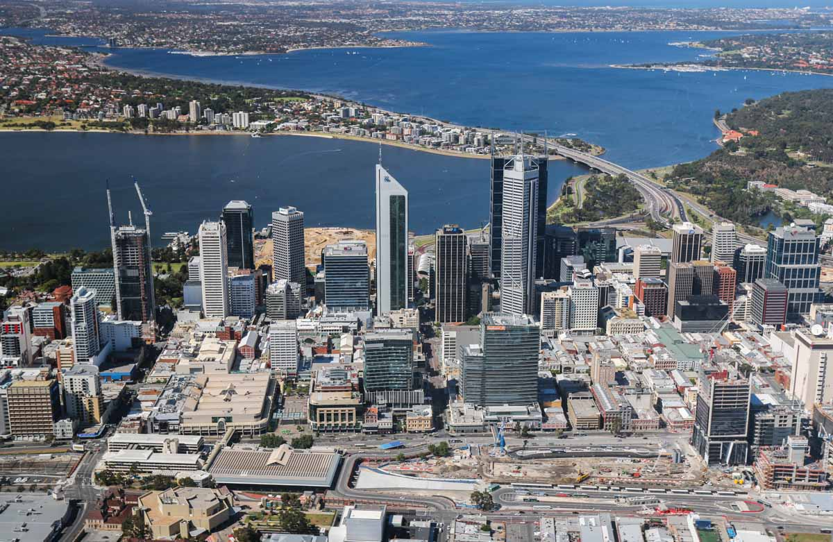 Perth city, South Perth, Swan River, and Kings Park, seen from VH-ICE Cirrus SR22 GTS G5 (MSN 4063) owned by Andrew Dean - Sat 15 November 2014. View facing SSW. In the foreground just right of the Horseshoe Bridge is the construction work to bury the rail lines underground. Barrack Street, Forrest Place and William Street also visible. Photo © David Eyre