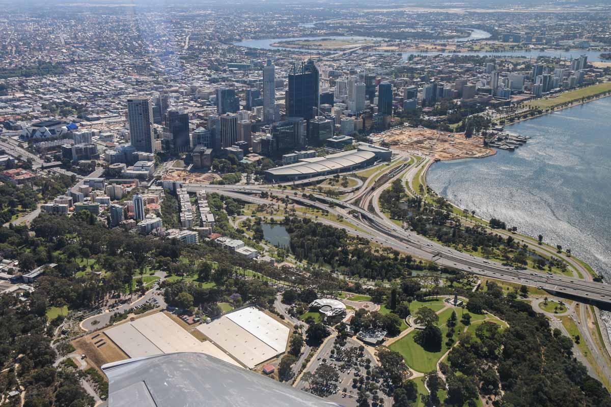 Kings Park, Perth city, and Swan River, seen from VH-ICE Cirrus SR22 GTS G5 (MSN 4063) owned by Andrew Dean - Sat 15 November 2014. View facing ENE. Kings Park War Memorial visible lower right. Construction of Elizabeth Quay visible next to Barrack Street Jetty. Photo © David Eyre