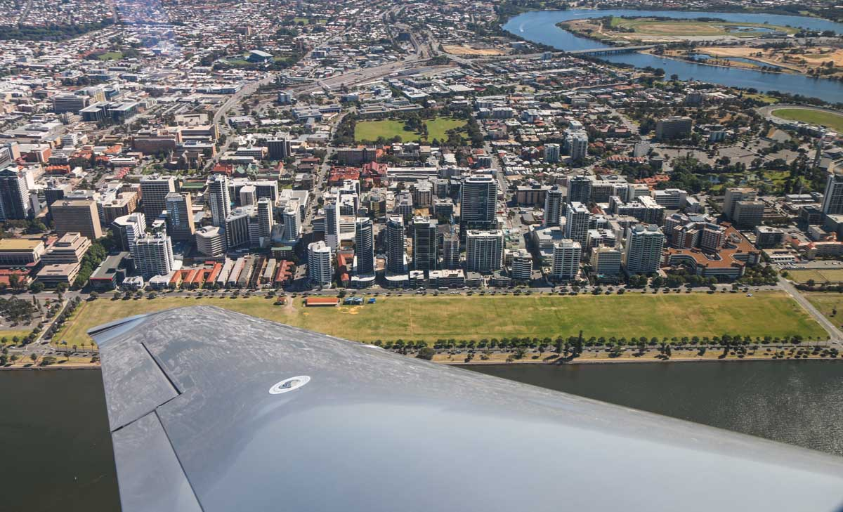 Langley Park, Perth city, East Perth, seen from VH-ICE Cirrus SR22 GTS G5 (MSN 4063) owned by Andrew Dean - Sat 15 November 2014. View facing NNE. The western third of Langley Park was used as Perth's first airport from late 1919 to January 1924. Upper right is Belmont Park Racecourse, which was where the first aircraft flight in Western Australia was made in 1911 by John J Hammond in a Bristol Boxkite. Norman Brearley also used a small strip between the racecourse and the river as his first airstrip, before moving to Langley Park. Photo © David Eyre