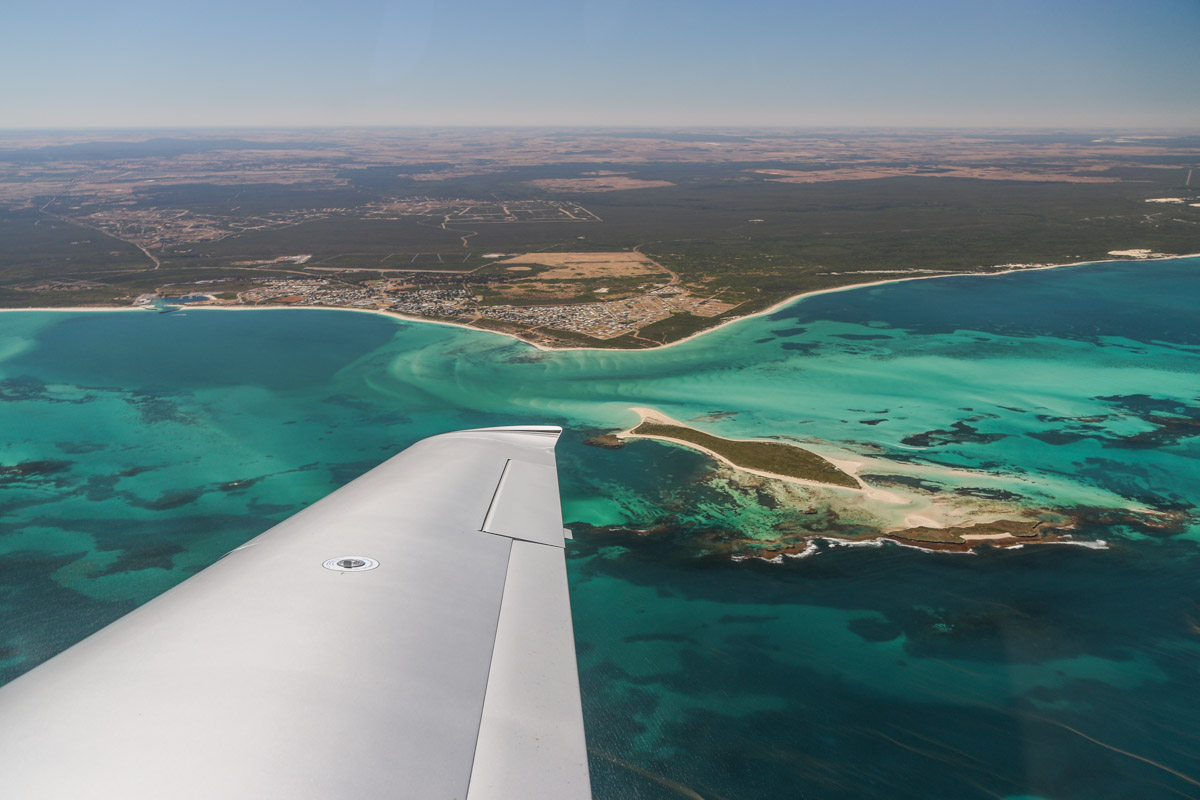 Jurien Bay, seen from VH-ICE Cirrus SR22 GTS G5 (MSN 4063) owned by Andrew Dean - Sat 15 November 2014. View facing east. Jurien Bay is a tourism and crayfishing town, located 220km north of Perth. The fish-shaped island is Boullanger Island, with Whitlock Island slightly nearer to the camera. Photo © David Eyre