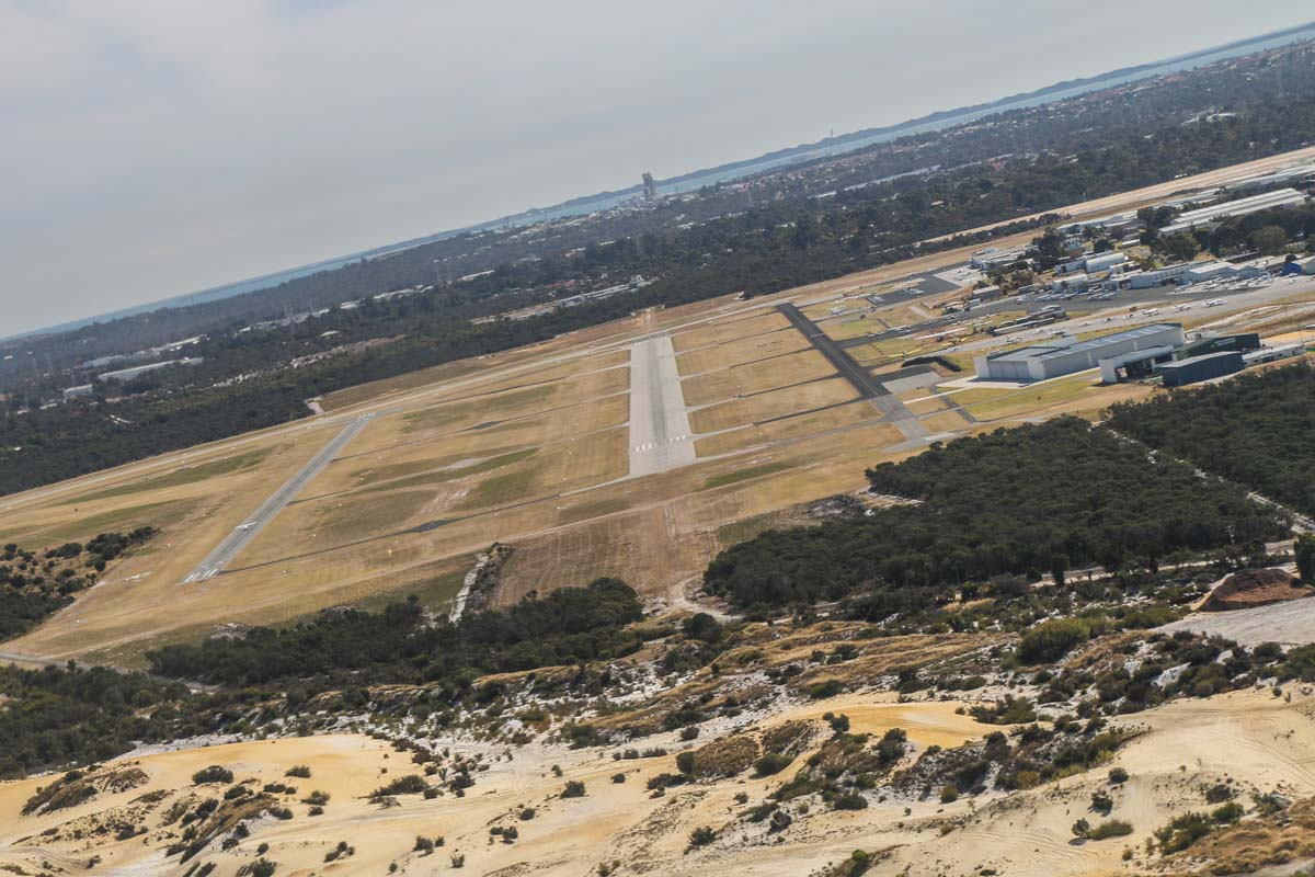Jandakot Airport runway 24R, seen from VH-ICE Cirrus SR22 GTS G5 (MSN 4063) owned by Andrew Dean - Sat 15 November 2014. View facing southwest as we turned onto final approach to runway 24R at 3:27pm. Photo © David Eyre
