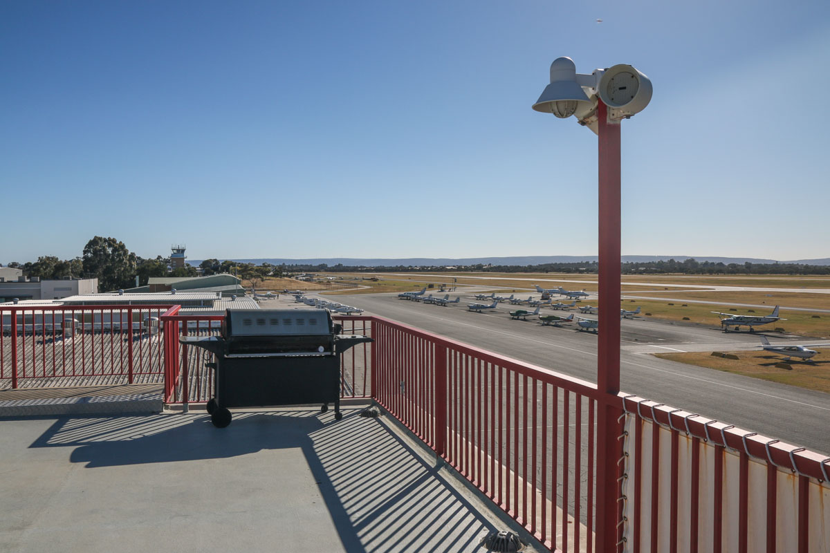Royal Aero Club of Western Australia building, top floor viewing area, facing northeast. Morning photo. Control tower at left. China Southern WA Flying College and Air Australia International aprons visible. Runway 06L/24R is at centre right. Jandakot Airport - Sat 15 November 2014. Photo © David Eyre