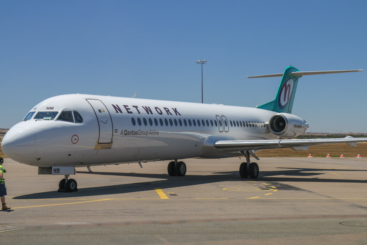 VH-NHM Fokker 100 (MSN 11449) of Network Aviation, at Geraldton Airport - Sat 15 November 2014. Just arrived from Perth at 10:47am, operating a flight for QantasLink, instead of the usual Dash 8Q-400. Photo © David Eyre