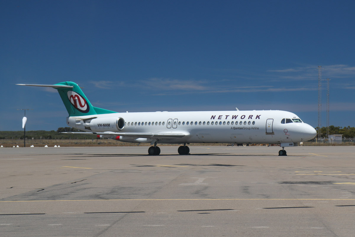 VH-NHM Fokker 100 (MSN 11449) of Network Aviation, at Geraldton Airport - Sat 15 November 2014. Arrived from Perth at 10:47am, operating a flight for QantasLink, instead of the usual Dash 8Q-400. Photo © David Eyre