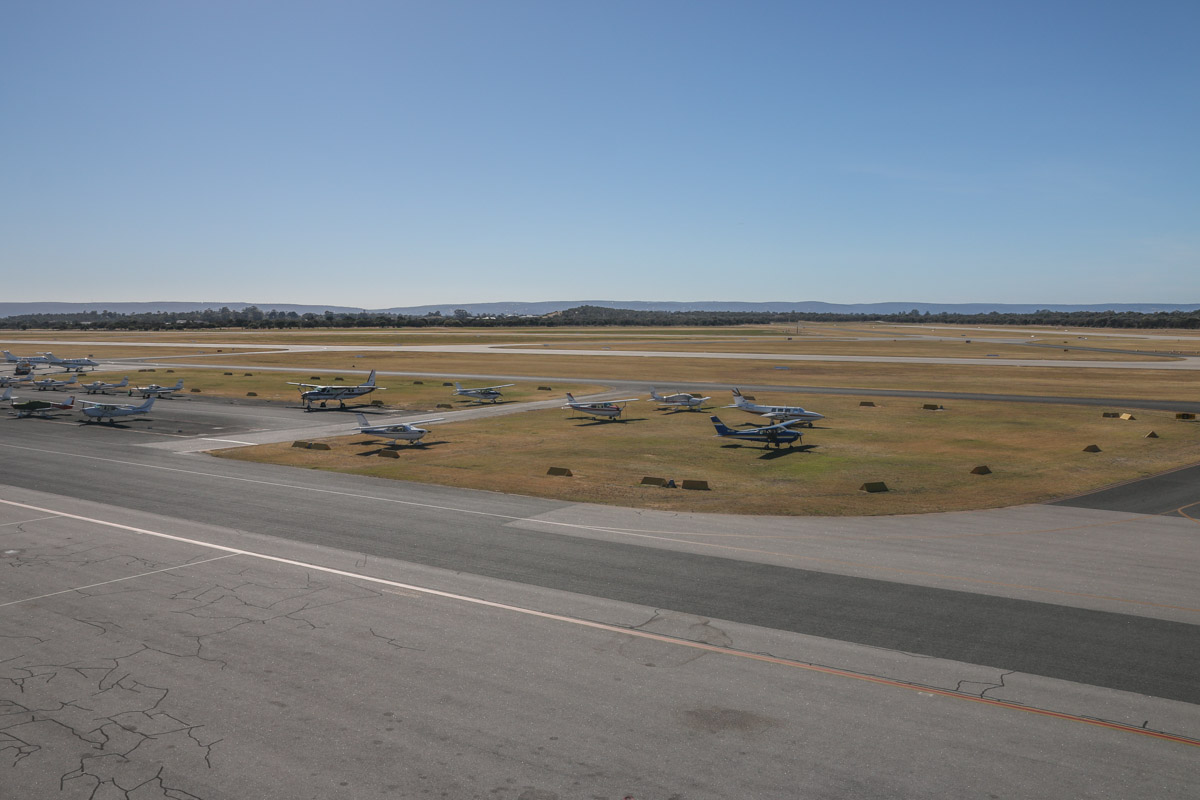 View east-south-east from Royal Aero Club of Western Australia building, top floor viewing area. Morning photo using 17-55mm wide angle zoom lens at 38mm. China Southern WA Flying College and visiting aircraft apron areas. Runways also visible. Jandakot Airport - Sat 15 November 2014. Photo © David Eyre