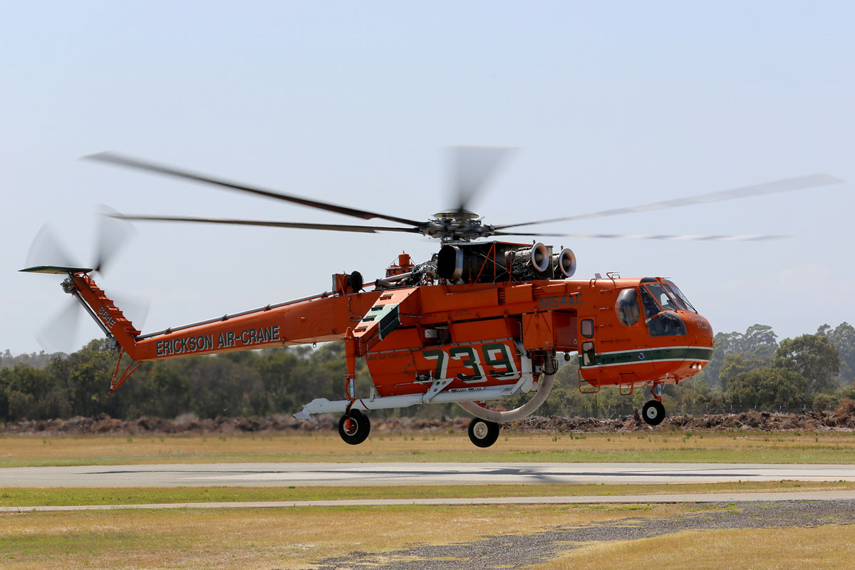 N154AC Sikorsky S-64E Skycrane (MSN 64-037), named 'Georgia Peach', of Erickson Air-Crane at Jandakot Airport – Sat 20 December 2014. This arrived by sea at Fremantle and was flown to Jandakot for refuelling. It is seen here departing at 9:44am to Serpentine Airfield, where it will be based. Under contract to the WA Government on firefighting duties for the 2014/2015 season. Built in 1967. Delivered to the US Army in February 1968 as 68-18435, as a CH-54A Tarhe. Last served with 1160 Aviation Company, Georgia Army National Guard. Retired from military service in late 1980s. On 26 March 1992, registered to Erickson Air Crane Co, Central Point, Oregon, USA as N154AC. Photo © Matt Hayes
