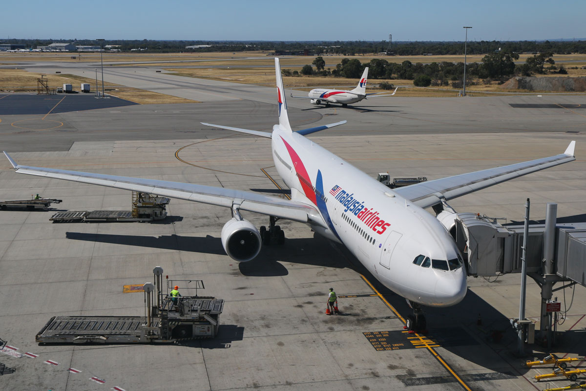 9M-MTA Airbus A330-323X (MSN 1209) and 9M-MXG Boeing 737-8H6 (MSN 40134/3873) of Malaysia Airlines, at Perth Airport – Sun 28 December 2014. Two Malaysia Airlines aircraft together at Perth. 9M-MTA has just parked at Bay 53 after arriving as flight MH125 from Kuala Lumpur at 3:02pm. Behind is 9M-MXG, taxying out for departure as flight MH120 to Kota Kinabalu. Photo © David Eyre