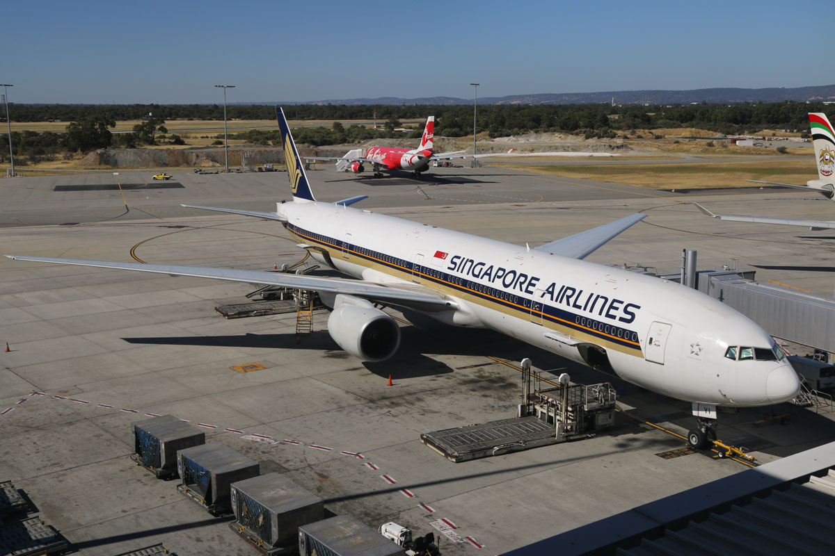 9V-SYI Boeing 777-312 (MSN 32327/484) of Singapore Airlines and 9M-XXD Airbus A330-343 (MSN 1066), named 'Soaring Xpectations' of Air Asia X at Perth Airport – Sun 28 December 2014. 9V-SYI: Singapore Airlines has been using some 777-300s and a -300ER on some of the SQ223/214 services recently. Flight SQ214 to Singapore is seen here parked at Bay 54 awaiting departure. 9M-XXD: This aircraft blew a tyre while landing as flight D7236 from Kuala Lumpur at 5:48am today. This also caused a hydraulic leak and the aircraft taxied off the runway at taxiway L2 and passengers had to wait aboard until buses could take them to the terminal. The aircraft was then towed to Bay 60 and the blown tyre was removed. Spare parts were flown in aboard the afternoon D7232 flight, and 9M-XXD finally departed as flight D7237D at 10.14pm the next day (29 December). To the right is A6-EYT Airbus A330-243 (MSN 1486) of Etihad, awaiting departure as EY487 to Abu Dhabi. Photo © David Eyre