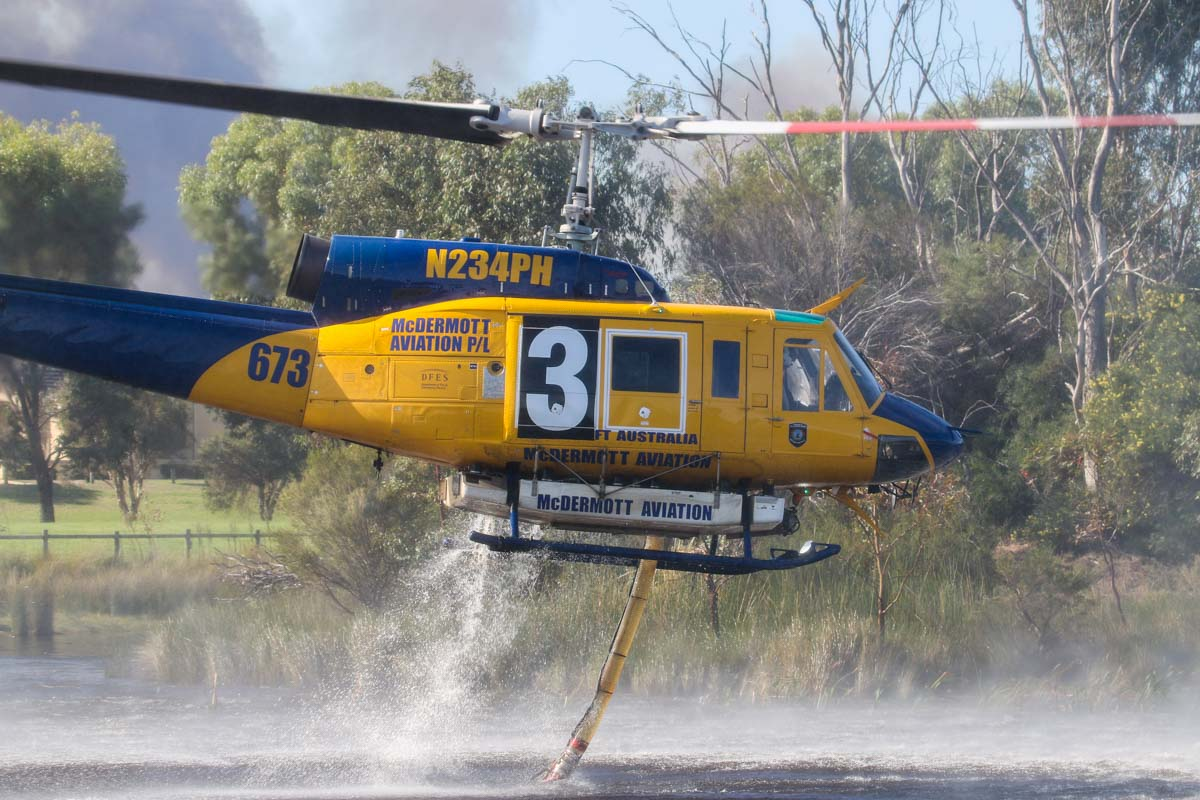 N234PH / HELITAK 673 Bell 214B-1 BigLifter (MSN 28050) of McDermott Aviation, at Warradale Park, Landsdale – Sun 5 April 2015. Filling up with water from the lake, whilst fighting a fire at the Gnangara pine plantation. N234PH is being operated for the WA Department of Fire and Emergency Services, for firefighting. Built in 1977. Ex N5750L, N234PH, 756 (Royal Air Force of Oman), VH-LYH. Photo © David Eyre
