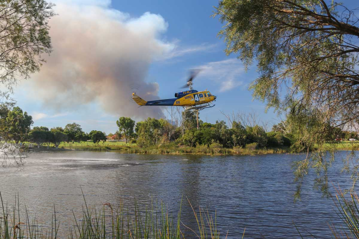 P2-MLJ / HELITAK674 Bell 214B1 BigLifter (MSN 28066) owned by McDermott Aviation, at Warradale Park, Landsdale – Sun 5 April 2015. Filling up with water from the lake, whilst fighting a fire at the Gnangara pine plantation - the smoke from the fire is visible behind. P2-MLJ is being operated for the WA Department of Fire and Emergency Services, for firefighting. Built in 1981, ex N2179R, JA9304, N4410N, C-GTWG, F-GJKZ, N214JL. Photo © David Eyre