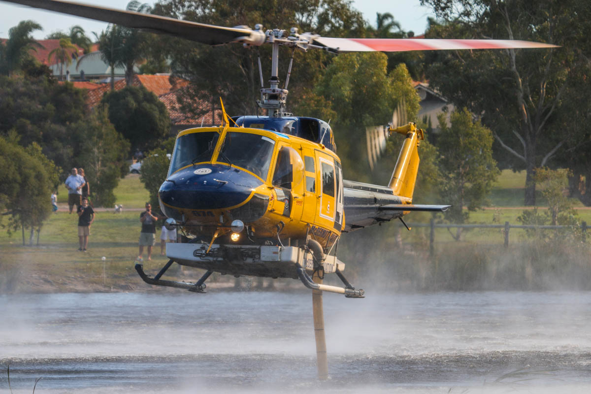 P2-MLJ / HELITAK674 Bell 214B1 BigLifter (MSN 28066) owned by McDermott Aviation, at Warradale Park, Landsdale – Sun 5 April 2015. Filling up with water from the lake, whilst fighting a fire at the Gnangara pine plantation. P2-MLJ is being operated for the WA Department of Fire and Emergency Services, for firefighting. Built in 1981, ex N2179R, JA9304, N4410N, C-GTWG, F-GJKZ, N214JL. Photo © David Eyre
