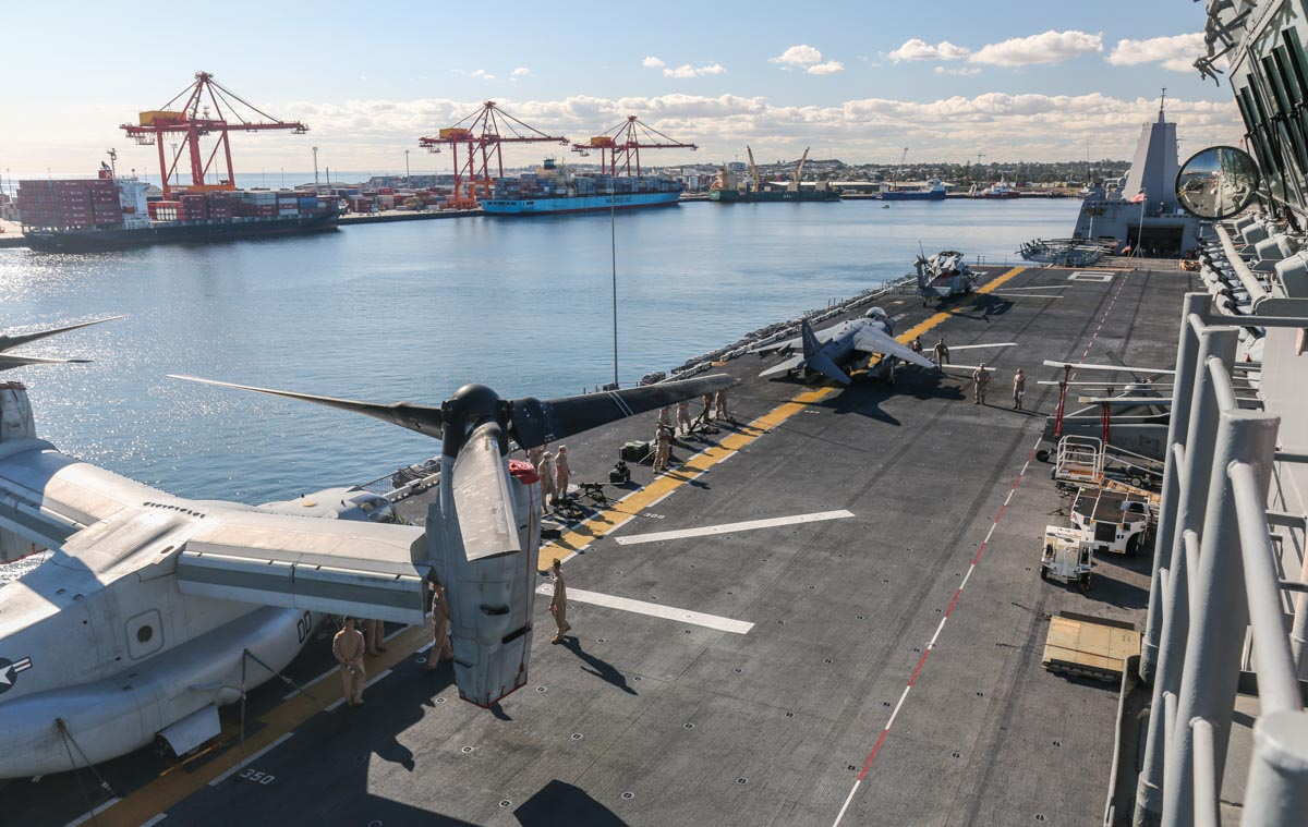 Forward end of the flightdeck of USS Bonhomme Richard (LHD-6), at Fremantle - Fri 26 June 2015. Viewed from the bridge. Visible aircraft include some Bell Boeing MV-22B Osprey tilt rotors, one McDonnell Douglas AV-8B+ (R) Harrier II Plus and two Sikorsky MH-60S Seahawks. In the upper right of the photo is USS Green Bay (LPD-20) with four AH-1W Super Cobras and three UH-1Y Venoms aboard. Photo © David Eyre
