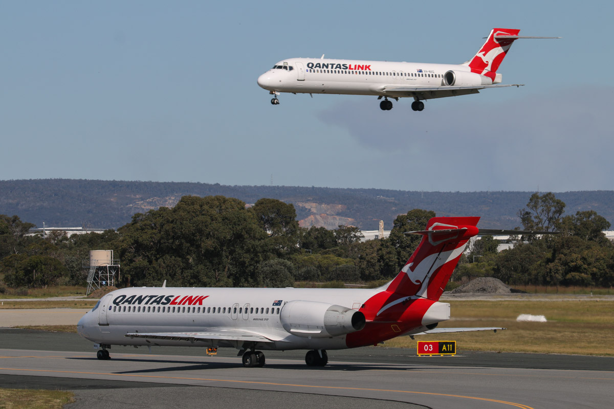 VH-NXH (foreground) (MSN 55055/5014) and VH-NXG (MSN 55057/5020) Boeing 717-2K9 of QantasLink, at Perth Airport – Thu 17 September 2015. VH-NXH is holding on taxiway A11 at 2:52pm for departure on runway 03 as flight QF1806 to Paraburdoo, whilst VH-NXG lands as QF1829 from Port Hedland. Photo © David Eyre