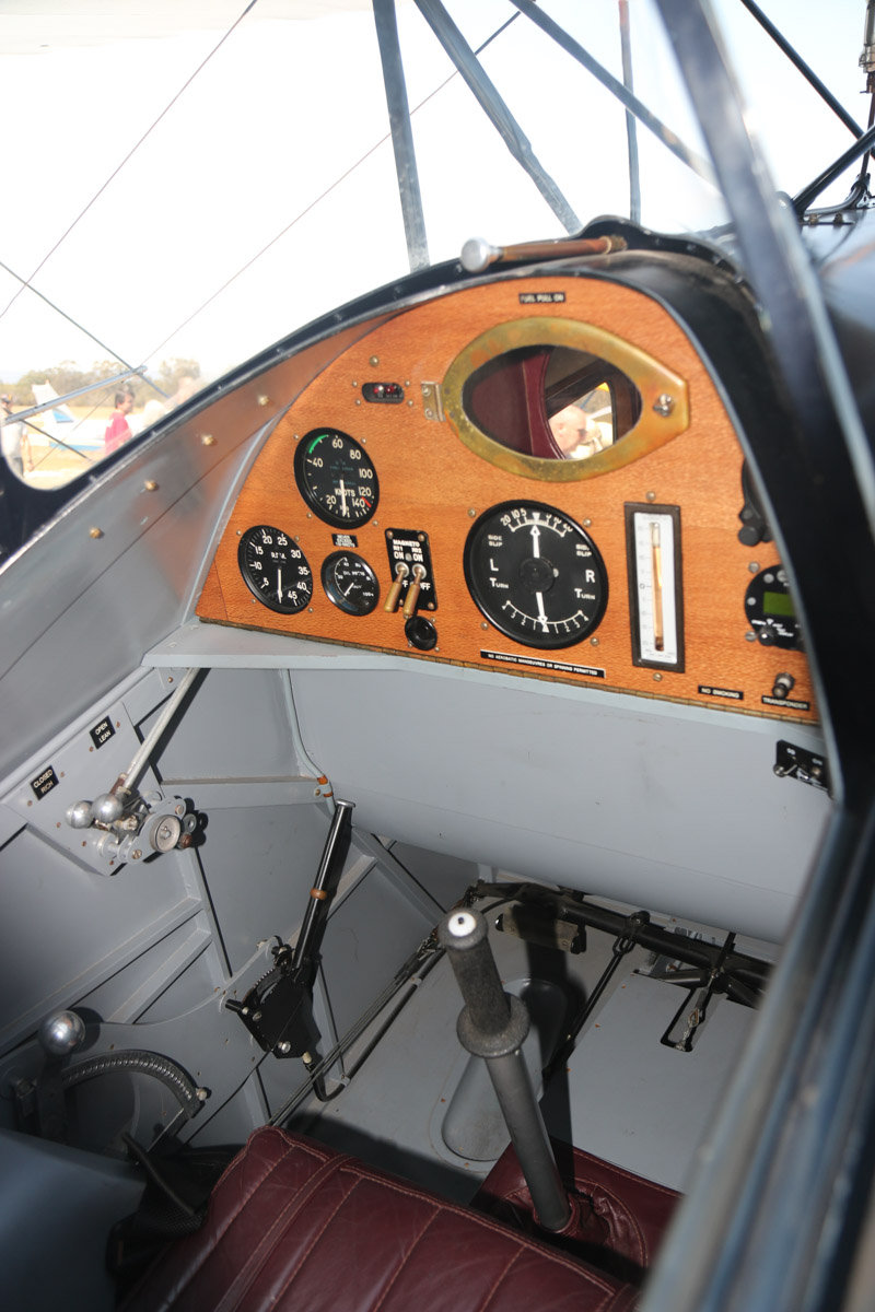 VH-USJ De Havilland DH-83 Fox Moth (MSN 4058) owned by Bert Filippi, at SABC Annual Fly-in, Serpentine Airfield - Sun 27 September 2015. This is the cockpit, which has a small oval window to see into the passenger cabin, which has seating for four passengers. Built in 1933 by De Havilland at Stag Lane Aerodrome, Edgeware, UK, and registered in 1933 as G-AECB to Scottish Motor Traction Co. Ltd., Edinburgh. In 1935, it was shipped to Fremantle, WA for MacRobertson Miller Airlines (MMA), and was registered VH-USJ. It was based in Port Hedland and operated by MMA for Australian Aerial Medical Service (AAMS), and in 1941 was sold to them. AAMS later became the Flying Doctor Service (WA Section) Inc. It was sold in 1961 and was damaged in an accident in 1964. After a series of owners and locations awaiting rebuild, in 1996, it was shipped to New Zealand and re-built. It flew again on 22 November 2002, registered as ZK-USJ, but still wearing VH-USJ. It returned to Australia in 2003 and was again registered VH-USJ. Photo © David Eyre