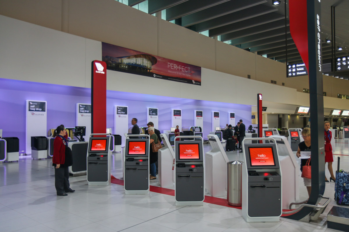 Terminal 1 Domestic on the first day of operations, Perth Airport - Sun 22 November 2015. Check-in area inside the terminal at 5:48am, 2 minutes after the doors opened. The first passengers are seen using the self check-in facilities. The new self bag drop systems are along the back wall. Virgin Australia staff can assist passengers using the new technology, if required. Photo © David Eyre