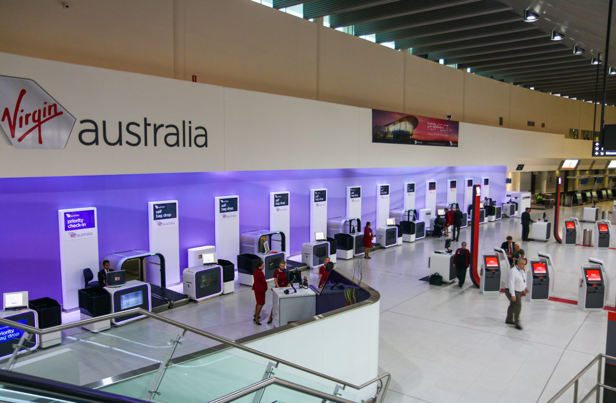 Terminal 1 Domestic on the first day of operations, Perth Airport - Sun 22 November 2015. Check-in area inside the terminal at 5:48am, 2 minutes after the doors opened. The first passengers are seen using the self check-in facilities. The new self bag drop systems are along the back wall. Virgin Australia staff can assist passengers using the new technology, if required. The international check-in area is visible in the background at the right of photo. Photo © David Eyre