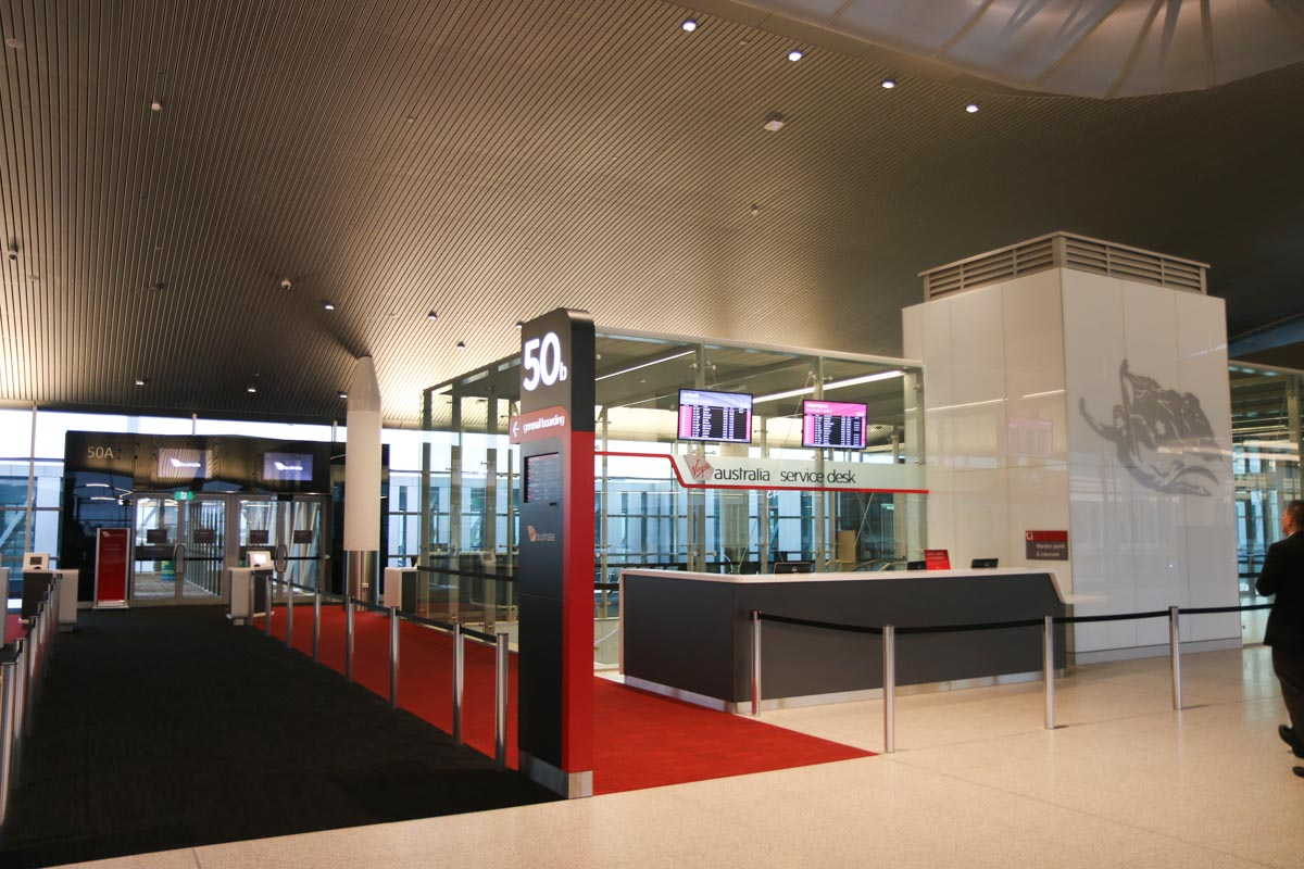 Terminal 1 Domestic on the first day of operations, Perth Airport - Sun 22 November 2015. Gate 50A and 50B. 50B is designed to switch between domestic and international flights, with international passengers segregated behind a glass partition. There are two Virgin Australia customer service desks, one at each end of the terminal. Photo © David Eyre