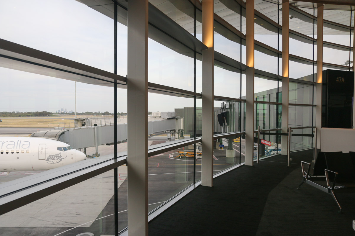 Terminal 1 Domestic on the first day of operations, Perth Airport - Sun 22 November 2015. The western end of the new Terminal 1 Domestic pier near gate 47A, which provides views of the runways and taxiways, and in this case, the city of Perth in the distance. Boeing 737-800 VH-YFF is visible outside. The double-glazed windows reduce noise, but may cause some reflections and distortion when photographing aircraft.