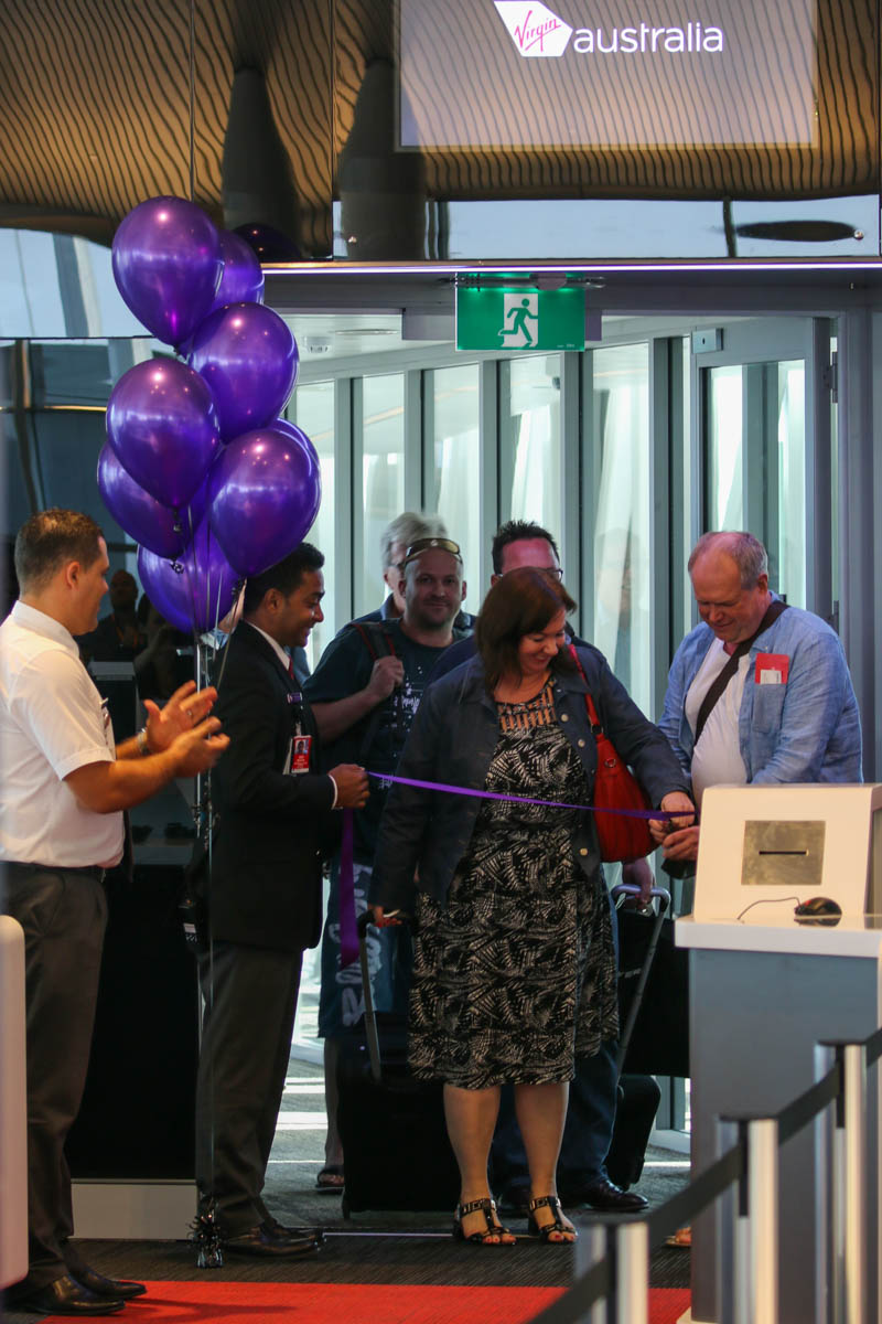 Terminal 1 Domestic on the first day of operations, Perth Airport - Sun 22 November 2015. A male passenger and female passenger share the honour of cutting the ribbon at gate 48A at 7:31am, after they arrived on the first flight to use the new terminal, flight VA713 from Adelaide, operated by Embraer E190 VH-ZPN. Photo © David Eyre