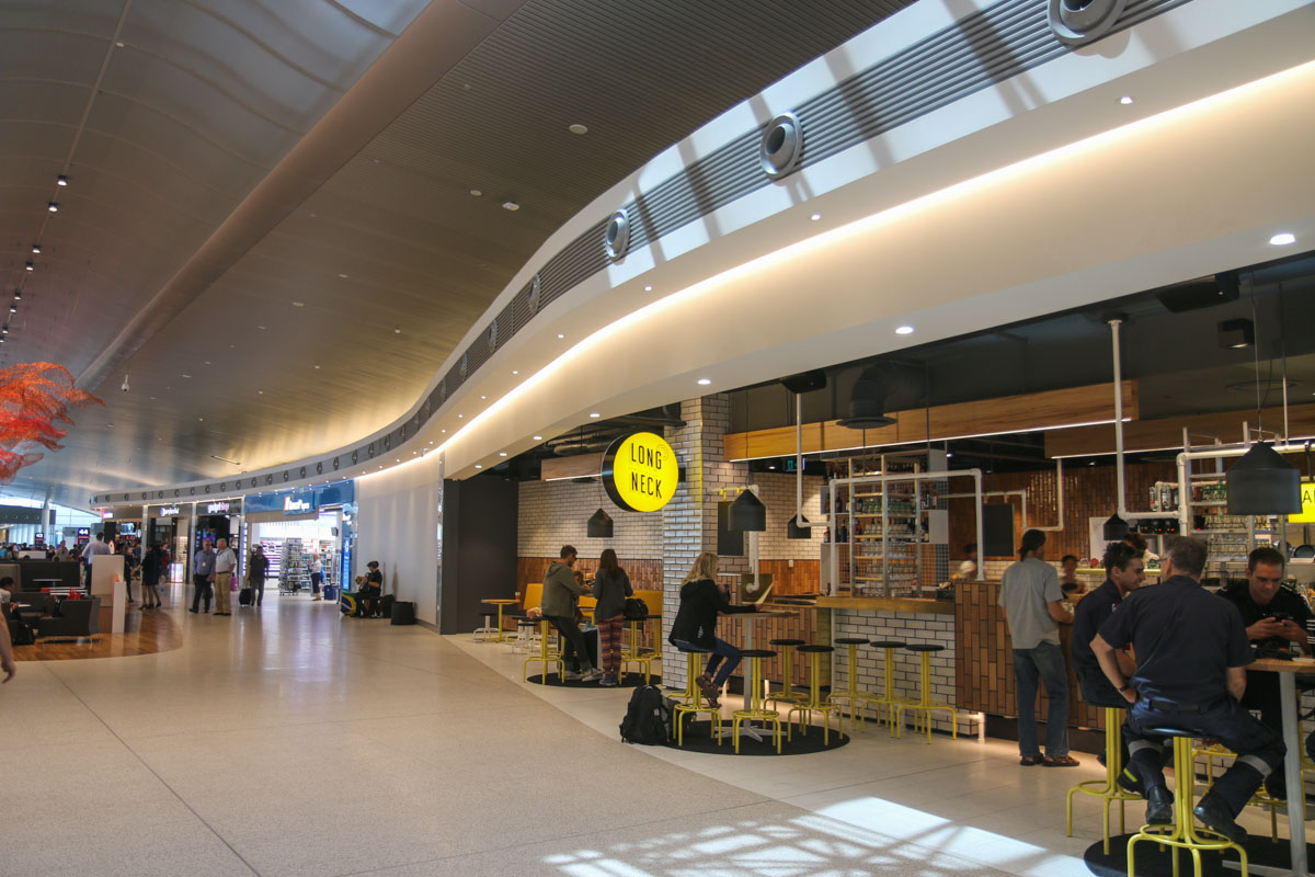 Terminal 1 Domestic on the first day of operations, Perth Airport - Sun 22 November 2015. View east, from the west end of the new Terminal pier, with a bar and chemist on the right. Photo © David Eyre