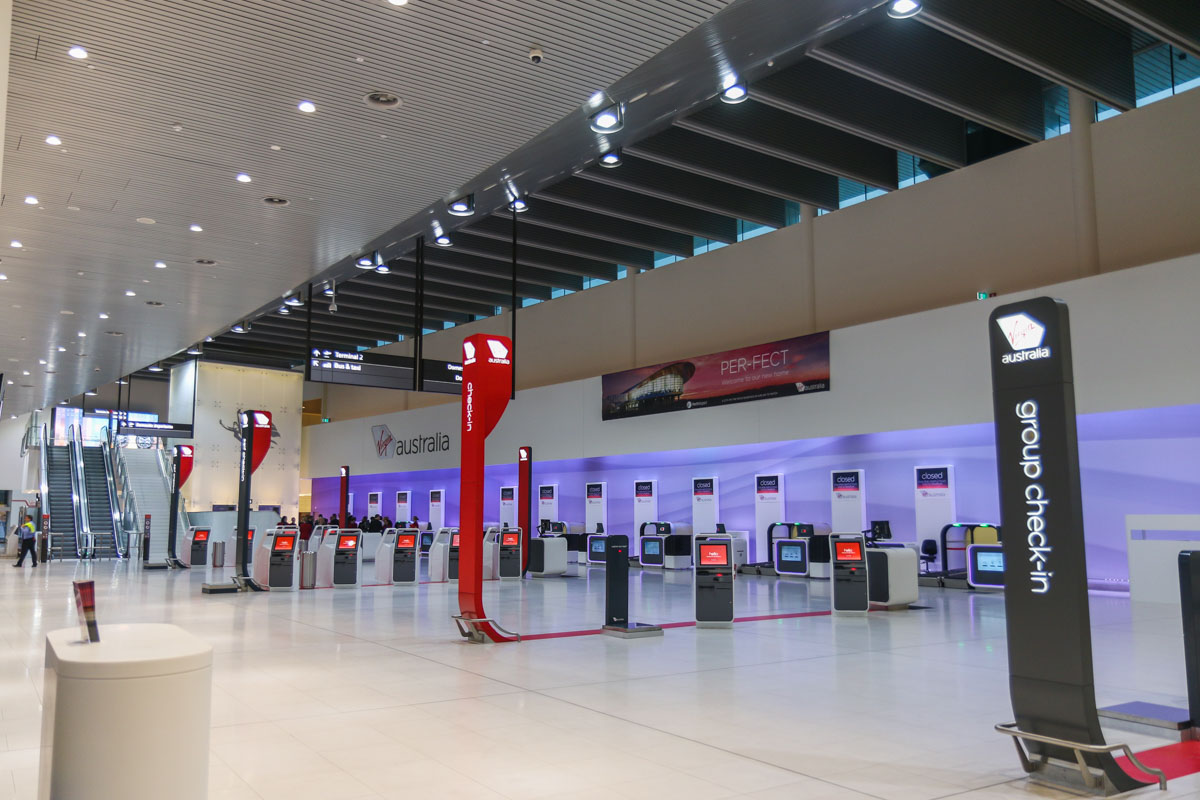 Terminal 1 Domestic on the first day of operations, Perth Airport - Sun 22 November 2015. Check-in area inside the terminal at 5:19am, 27 minutes before the doors opened for the first passengers. The orange screens of the self-serve check-in are visible, with the new bag drop systems along the back wall. Virgin Australia staff can assist passengers using the new technology, if required. Photo © David Eyre