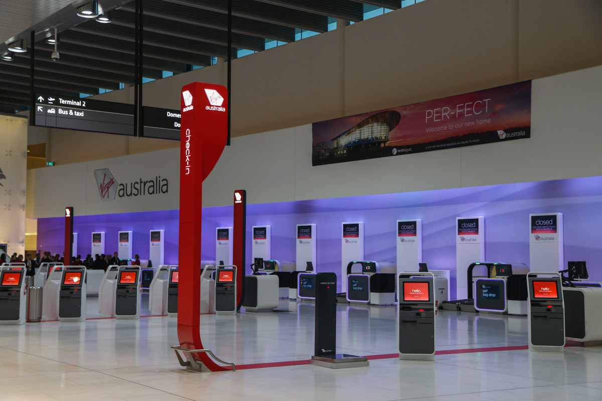 Terminal 1 Domestic on the first day of operations, Perth Airport - Sun 22 November 2015. Check-in area inside the terminal at 5:20am, 26 minutes before the doors opened for the first passengers. The orange screens of the self-serve check-in are visible, with the new bag drop systems along the back wall. Virgin Australia staff can assist passengers using the new technology, if required. Photo © David Eyre