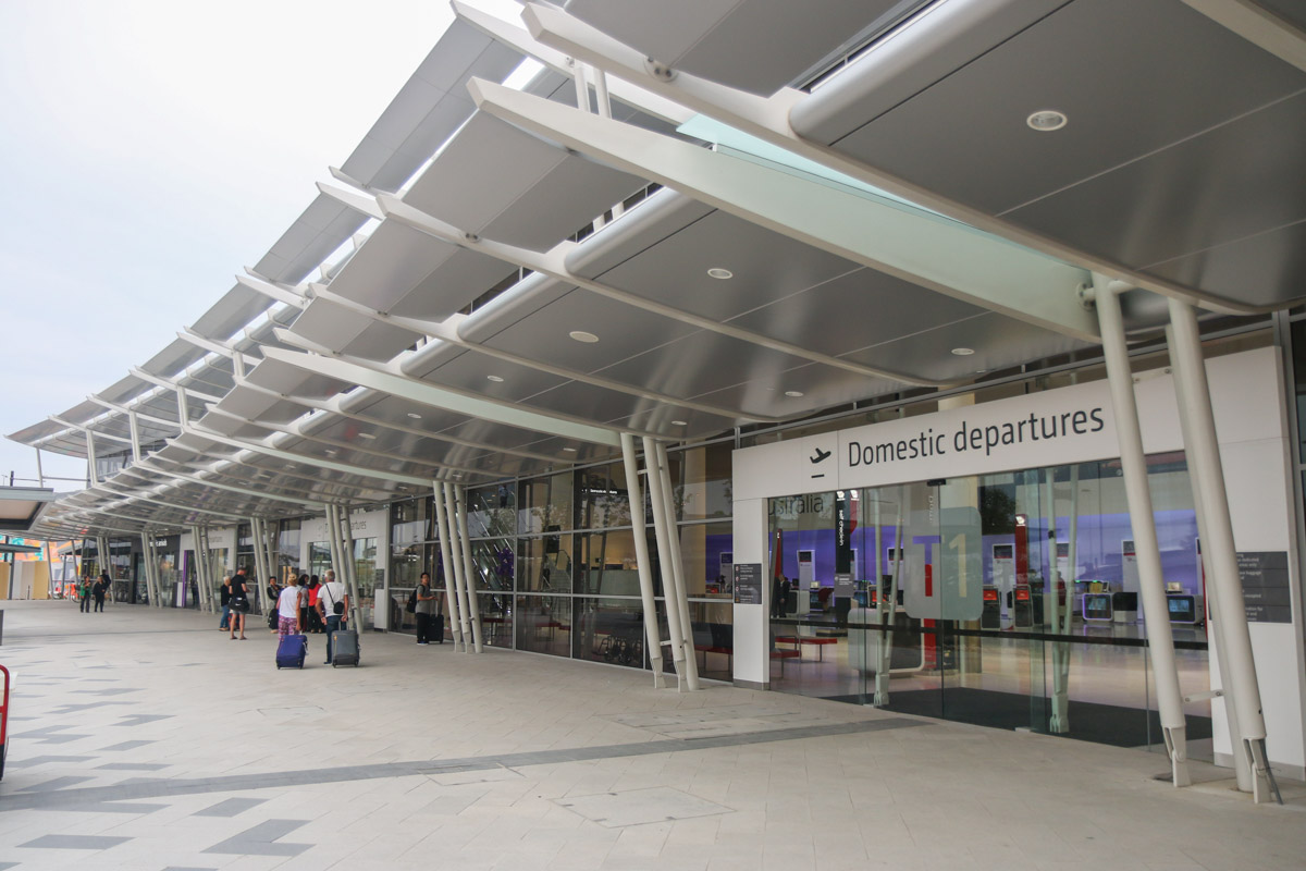 Terminal 1 Domestic on the first day of operations, Perth Airport - Sun 22 November 2015. Front of the terminal at 5:39am, 7 minutes before the doors opened for the first passengers, who can be seen gathering near the door. Photo © David Eyre